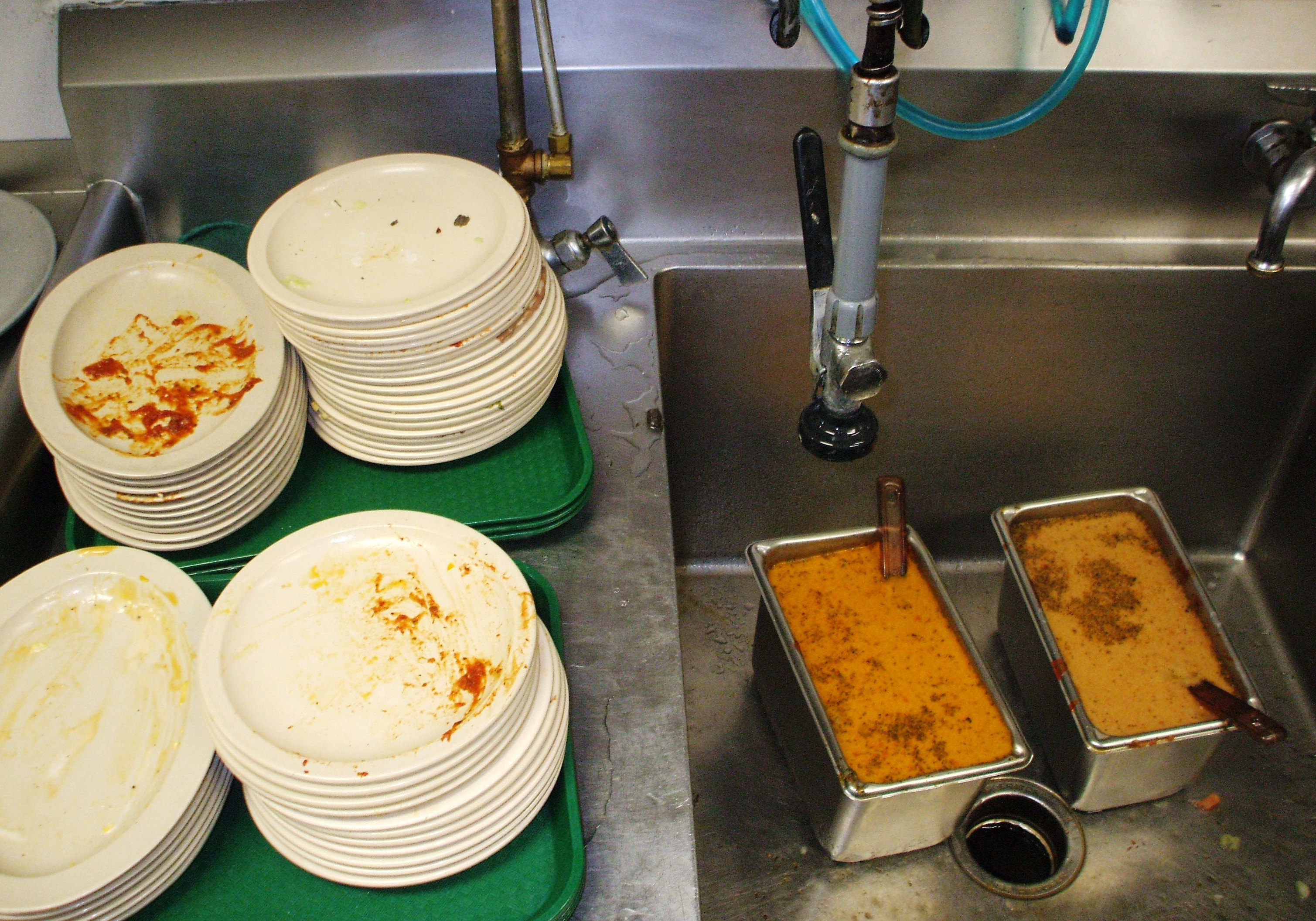 Fat, oil, and grease, and food solids on plates during clean-up in a commercial kitchen.